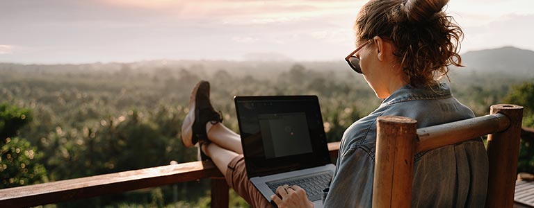 A woman taking an online certificate course outside with her laptop