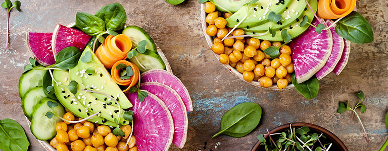 A plant-based salad bowl with chickpeas, avocado, carrot, cucumbers and radishes.