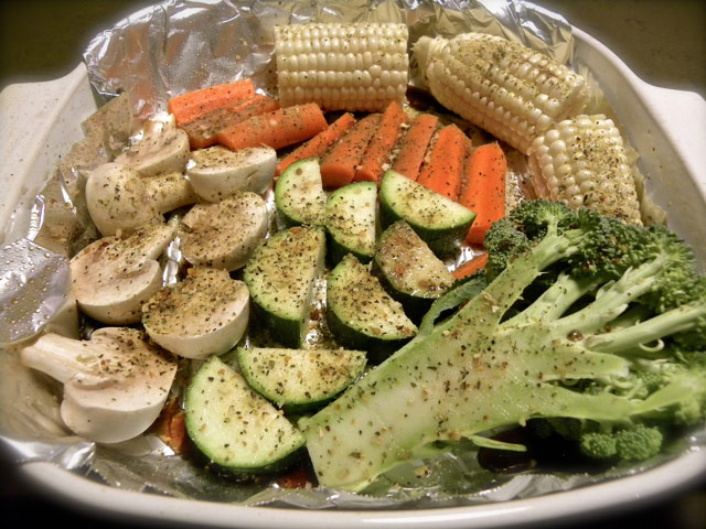 Multiple veggies sprayed, dusted, on foil in casserole dish before roasting